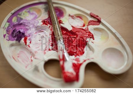 Smeared with the brush in the palette with paints. Red and purple paint