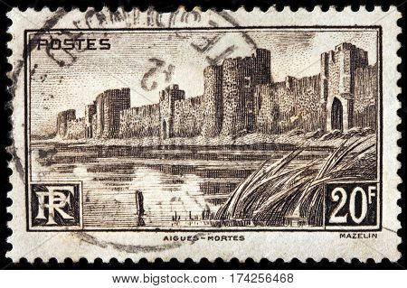LUGA RUSSIA - FEBRUARY 7 2017: A stamp printed by FRANCE shows view of medieval city walls surrounding the Aigues-Mortes town circa 1941