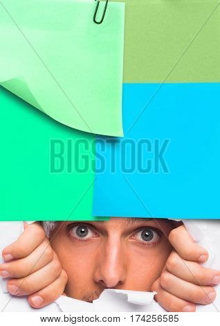 Digital generated image of man peeking through ripped paper hole