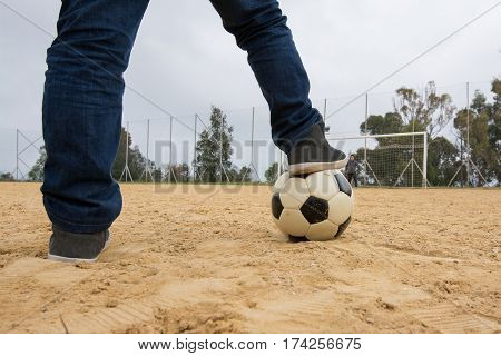 Little boy with his foot resting on top of a soccer ball on sand of a old field
