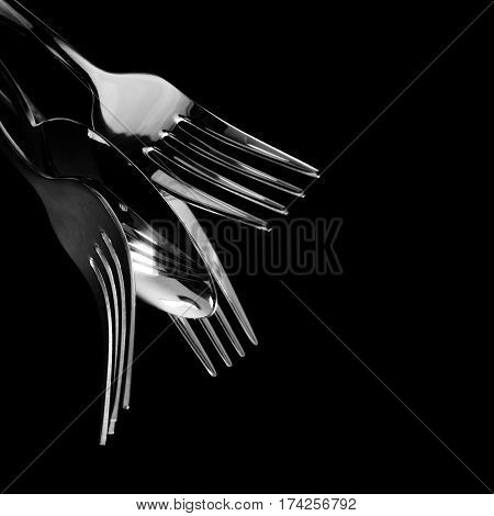 Abstract shapes with flatware on black background