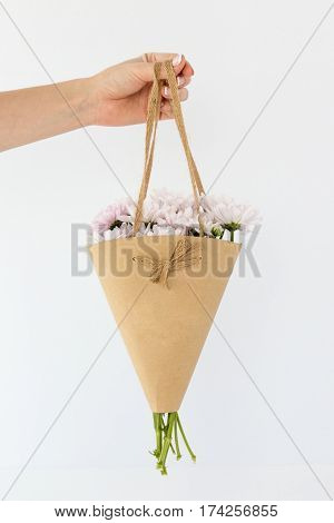 Crop photo of hand holding flowers in beige paper wrapper isolated on white background.