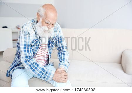 Senior man with pain in knee sitting on sofa