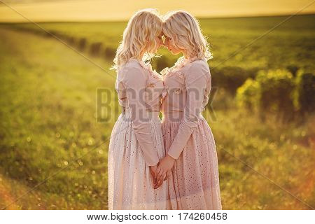 young beautiful twins of vintage dresses in the field