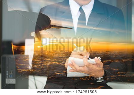 Double exposure of smart businessman writing notepad plan and beautiful night view airplane sunset flying in the sky evening flight : travel concept