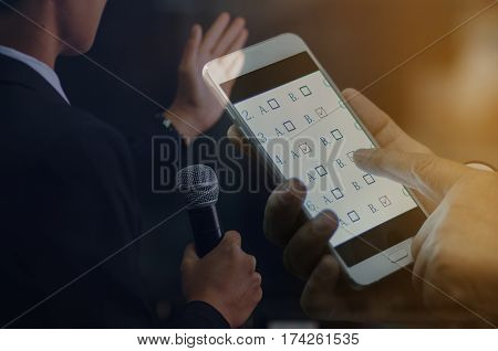 Double exposure of success businessman speech with microphone and student testing exercise exams answer on a tablet with multiple-choice questions by finger clicking : business and education concept