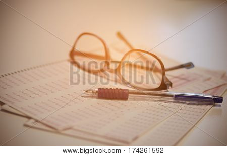 optical form of an examination with pen and glasses filling a standardized test form vintage tone