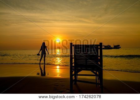 Happy Romantic woman Enjoying Beautiful Sunrise with chair on the Beach Vacation concept