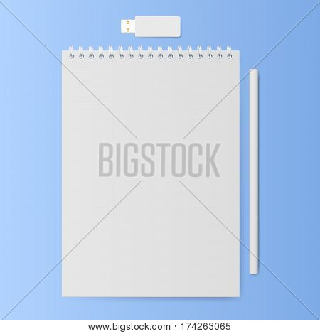 White notebook with a pencil and usb memory stick on a blue background.