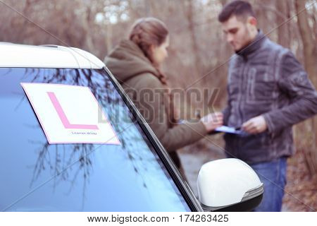 Learner driver sign on car windscreen. Blurred view of instructor and driver outdoors