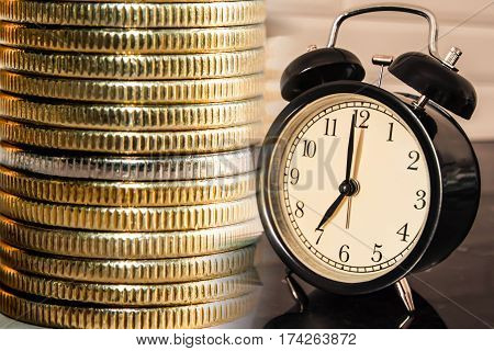 The clock on the background of the column of coins . The concept of time is money