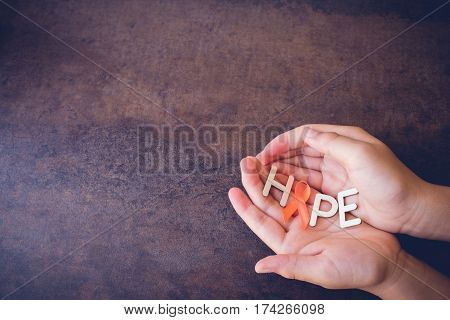 Hands Holding Hope With Orange Ribbons On Toning Background, Leukemia Awareness, Self Injury Awarene