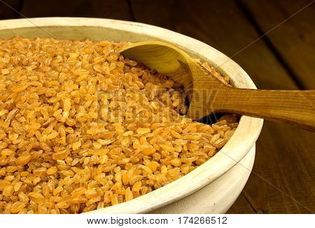 Dry bulgur wheat in a clay bowl with spoon on the table