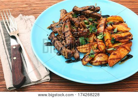 Homemade Slow Cooked Beef with Potatoes on wooden background