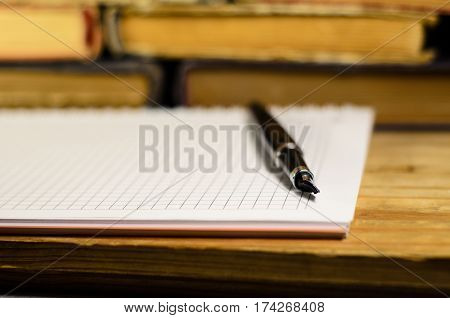 Notepad and fountain pen in front of many books