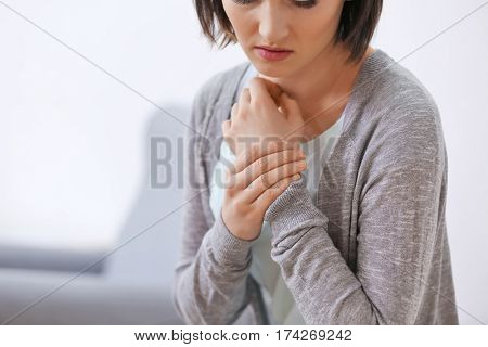 Young woman suffering from pain in wrist, close up