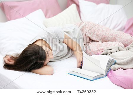 Young woman reading book on bed at home