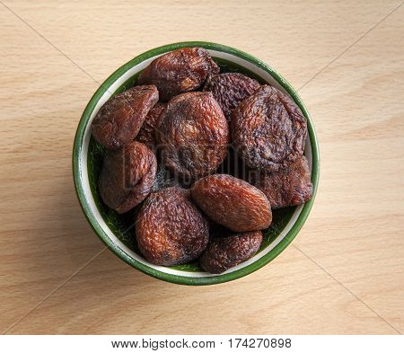 Dried apricots in an oriental bowl on a table