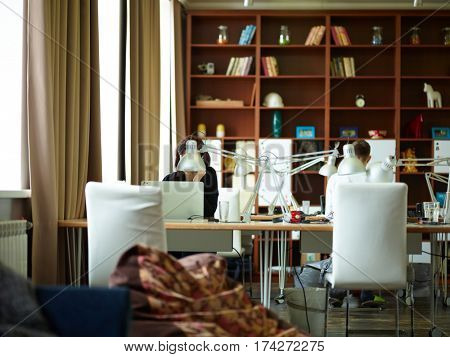 Wooden working desks with lamps against tall bookcases in modern office room with interior in warm brown tones