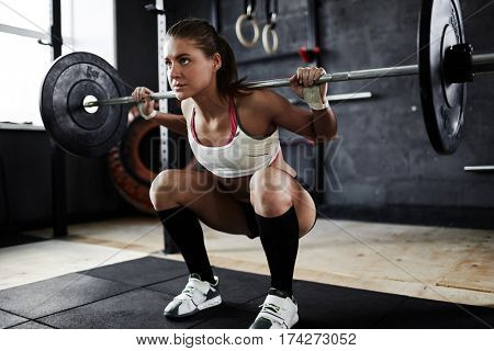 Intense workout in dark gym: strained young sportswoman performing shoulder press with heavy barbell, standing in start stance