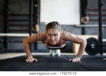 Intense workout in dark gym: front view of strained young sportswoman performing push us from floor looking at camera