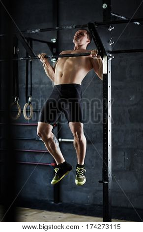 Intense workout in dark gym: strong muscular sportsman performing pull ups at wall mounted bar, his arm muscles strained and defined