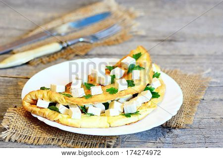 Low fat vegetarian tofu omelette. Delicious fried omelette stuffed with tofu and fresh parsley on a plate, fork and knife on vintage wooden background. Rustic style. Closeup