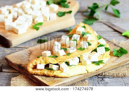 Healthy vegetarian tofu omelette. Homemade omelette stuffed with tofu and fresh parsley on a plate. Tofu cubes on cutting board. Vintage wooden background. Rustic style. Closeup