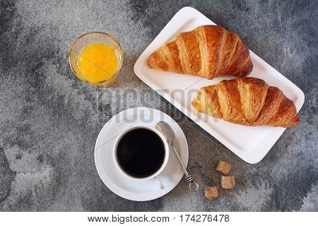 Two fresh croissants orange pulp juice and cup of coffee for breakfast. Top view