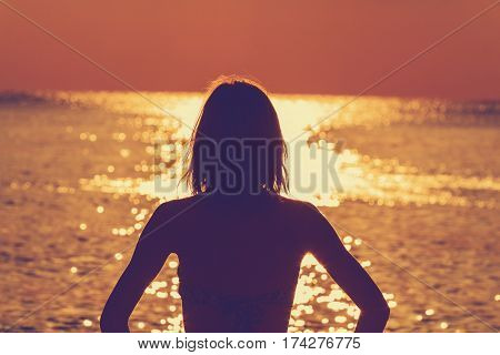 Lonesome girl watching the sunset over the sea / ocean.
