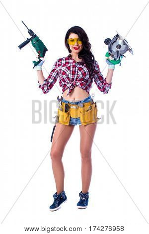 Project Satisfaction. Beautiful sexy brunette woman with a circular saw and perforator, isolated on white background