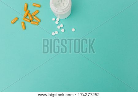 Opened Medicine Bottle, Capsules, And White Pills Copy Space