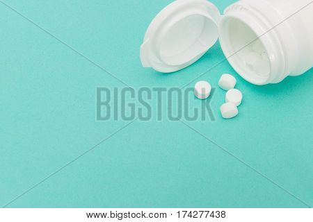 White Pills And Toppled Opened Medicine Bottle With Copy Space