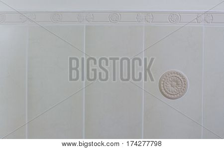 Decor element from plaster on the white tile background in the bathroom