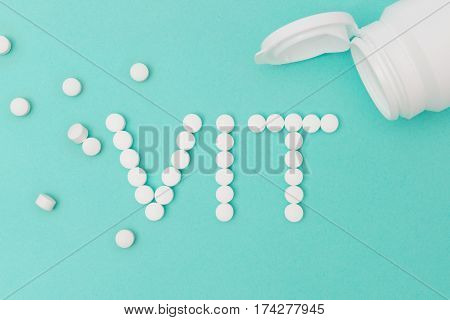 White Pills Forming The Word Vit With Bottle