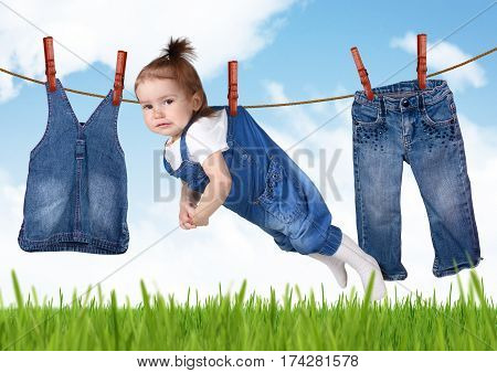 confused housework concept Funny child hanging on clothesline