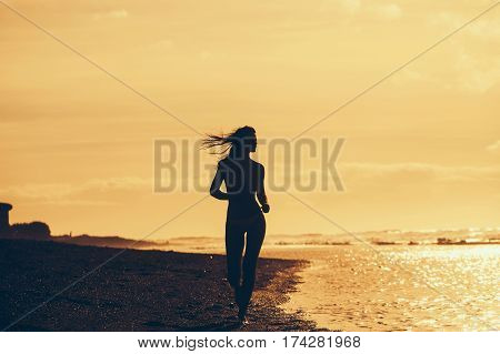 Pretty Girl In Yellow Swimsuit Running On Sandy Beach