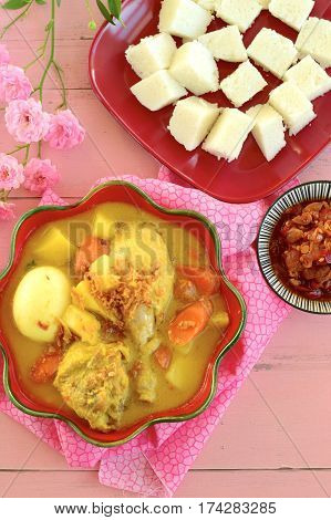 Opor ayam, chicken cooked in coconut milk and spices, served with lontong