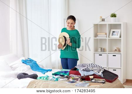 tourism, people and luggage concept - happy young woman with hat packing travel bag at home or hotel room