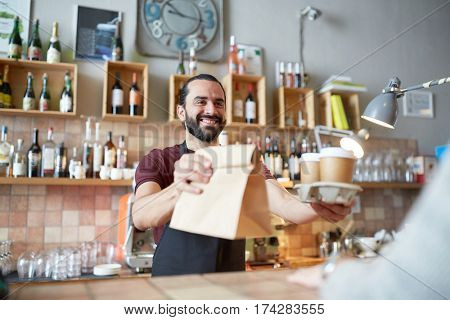 small business, people, takeaway and service concept - happy man or waiter giving bag and paper cups with hot drinks to customer at coffee shop