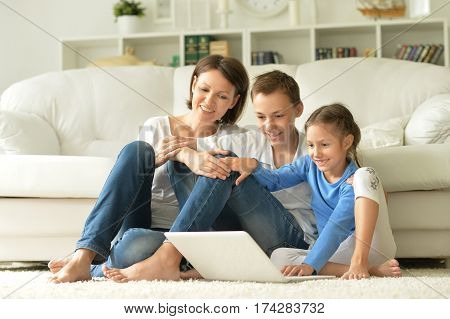 mother with son and daughter using laptop