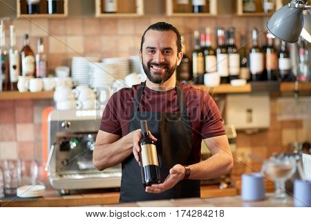 small business, alcohol drinks, people and service concept - happy man or waiter with bottle of red wine at bar