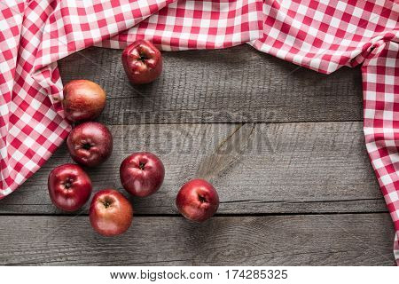 Ripe red apples on wooden board with red checkered napkin around and copy space.