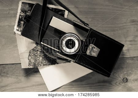 Vintage Old Retro Camera In Black Leather Bag With Old Photos On Wooden Board Top View.