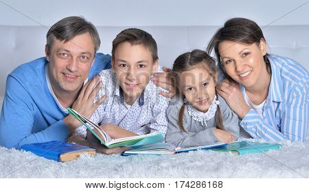 family reading books together on the floor