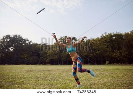 Young athletic girl playing with flying disc in the park. Professional player. Sport concept. Ultimate