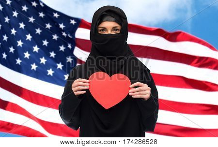 love, charity, immigration, valentines day and people concept - muslim woman in hijab holding red heart over american flag background