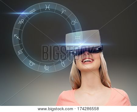 technology, augmented reality, astrology, horoscope and people concept - happy young woman in virtual headset or 3d glasses with signs of zodiac
