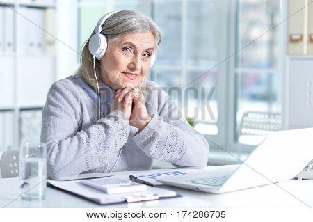 Portrait of a senior woman in headphones using laptop