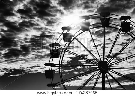 Ferris wheel silhouetted against an intense sky.